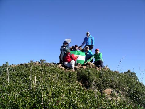El grupo posando en la cima con la bandera del club.